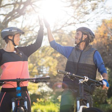 Happy biker couple giving high five while riding bicycle in countrysid